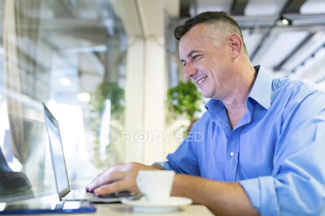Hombre de negocios sonriente usando el ordenador portátil mientras está sentado en la cafetería - foto de stock