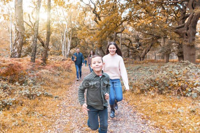 Fratello e sorella corrono felicemente mentre i genitori camminano dietro nel parco Cannock Chase durante l'autunno — Foto stock