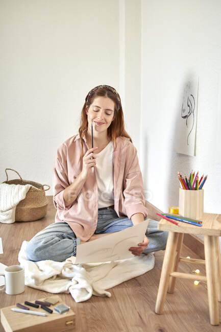 Smiling female artist contemplating while looking at drawing at home — Stock Photo
