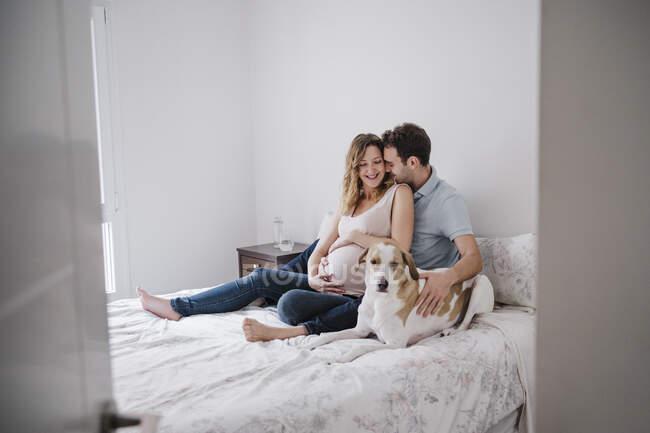 Hombre romancing con embarazada esposa mientras sentado con perro en cama visto a través de puerta - foto de stock
