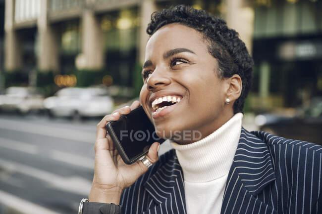 Felice giovane donna d'affari guardando lontano mentre parla su smart phone — Foto stock
