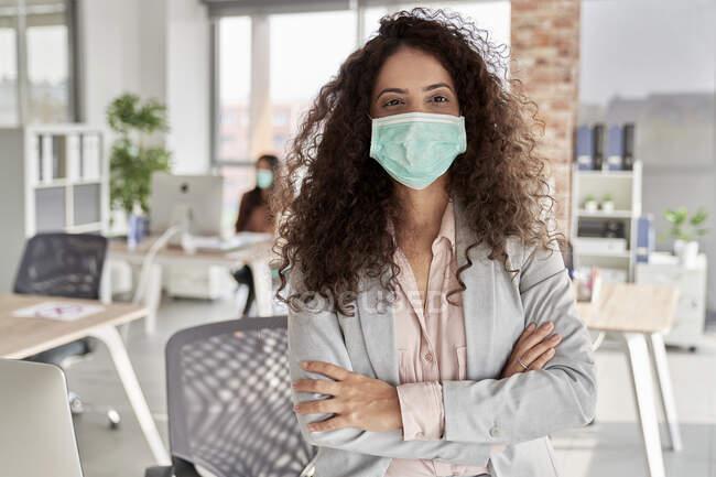 Молода жінка-професіонал з перехрещеними руками в офісі під час COVID-19 — стокове фото