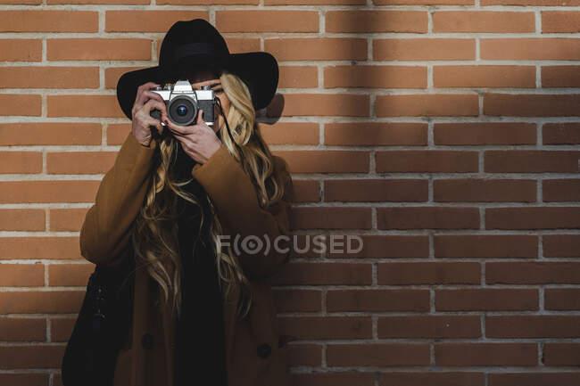 Mujer en sombrero filmando a través de la cámara mientras está de pie contra la pared de ladrillo - foto de stock