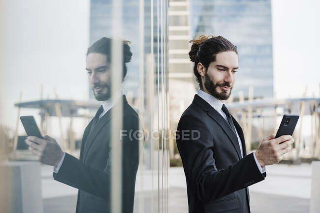 Young entrepreneur using mobile phone while standing by glass wall — Stock Photo
