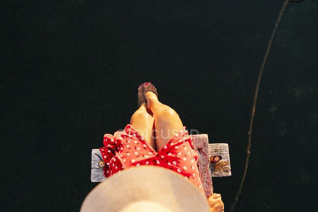 Woman wearing hat sitting with leg in water on edge of pier - foto de stock