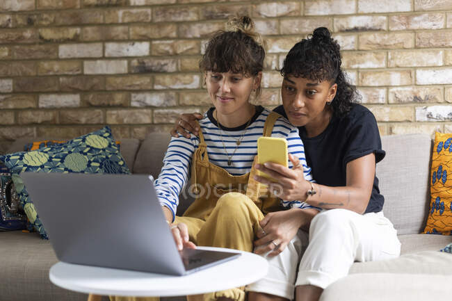 Woman using laptop while sitting by girlfriend using mobile phone at home — Stock Photo