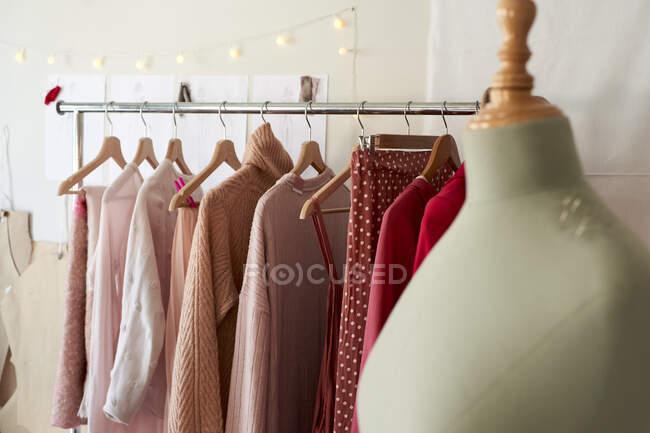 Modelo do fabricante de vestidos contra rack de roupas no estúdio de design — Fotografia de Stock