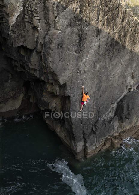 Scalatore di roccia maschio che si arrampica sulla scogliera sopra l'acqua — Foto stock