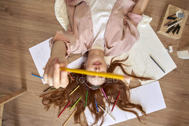 Playful female artist showing colored pencil while lying on floor in living room — Stock Photo