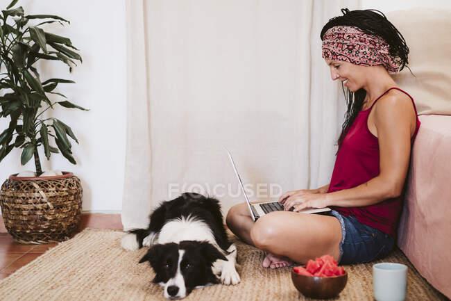 Жінка працює на ноутбуці, сидячи з собакою і фруктовою мискою вдома на килимі. — стокове фото