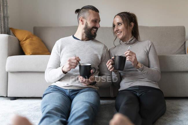 Улыбающаяся пара смотрит друг на друга, сидя дома на ковре в гостиной — стоковое фото
