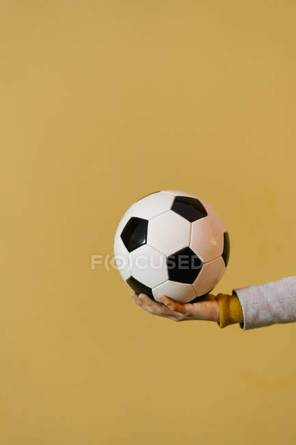 Чоловік тримає футбол проти жовтої стіни. — стокове фото