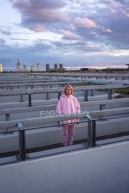 Молода жінка з рожевим волоссям у рожевому капелюсі стоїть на поручні. — стокове фото