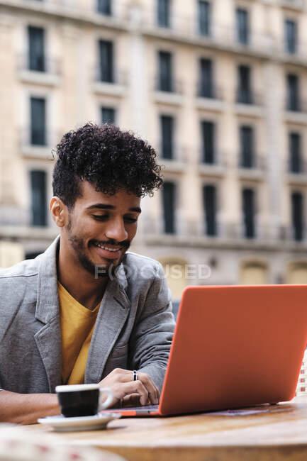 Uomo alla moda sorridente mentre si lavora sul computer portatile seduto a lato a piedi caffè — Foto stock