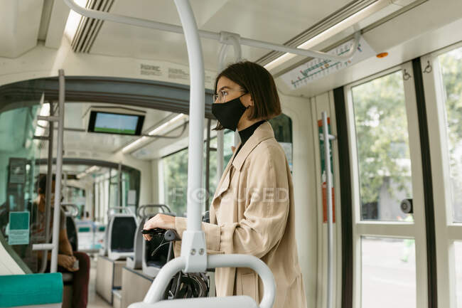 Mid adult woman wearing face mask looking away while traveling with electric push scooter in tram — Stock Photo