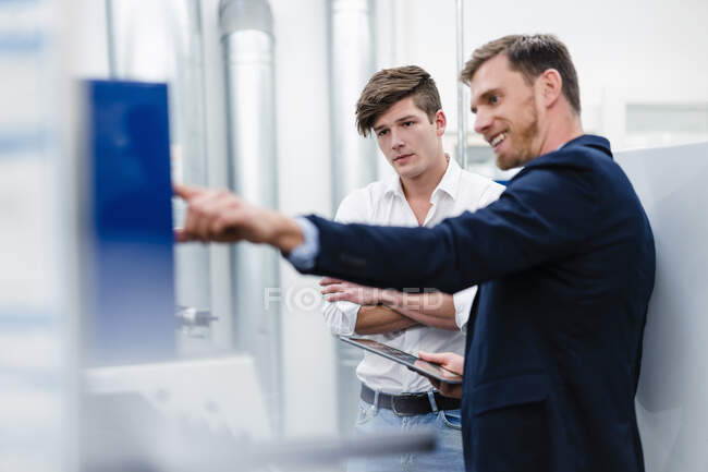 Smiling male professional with engineer operating machinery equipment in industry — Stock Photo