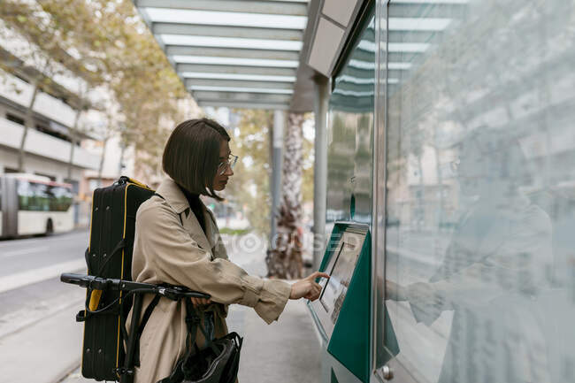 Woman with instrument case using ticket machine while standing with electric push scooter at tram station in city — Stock Photo