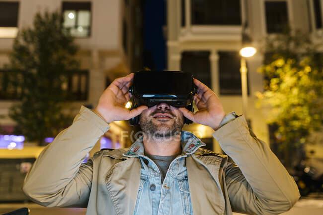 Man using virtual reality headset while sitting outdoors — Stock Photo