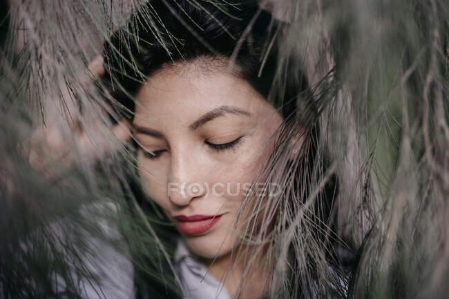 Улыбающаяся красивая женщина с закрытыми глазами посреди растительной иглы — стоковое фото