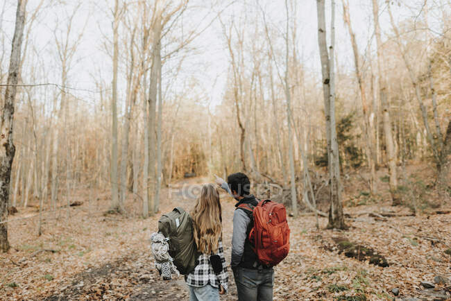 Young couple standing in forest during autumn hike — Stock Photo
