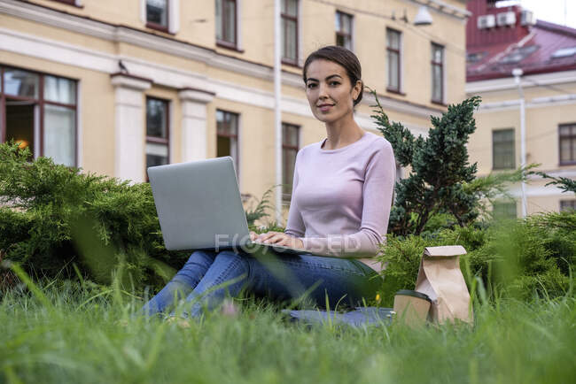 Emprendedora usando laptop mientras está sentada parque - foto de stock