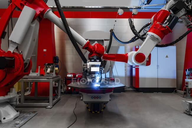 Автоматичні роботи зварюють метал на фабриці. — стокове фото