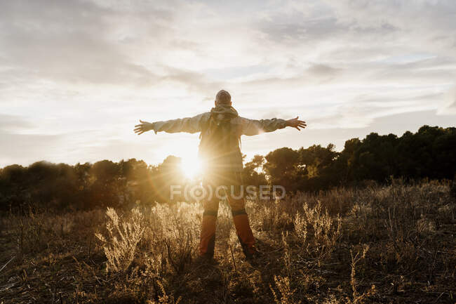 Senior male hiker standing on agricultural field with arms outstretched during sunset - foto de stock