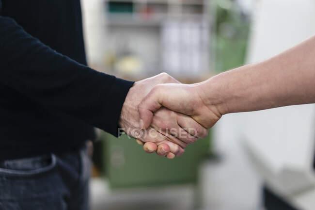 Colegas masculinos apertando as mãos na fábrica — Fotografia de Stock