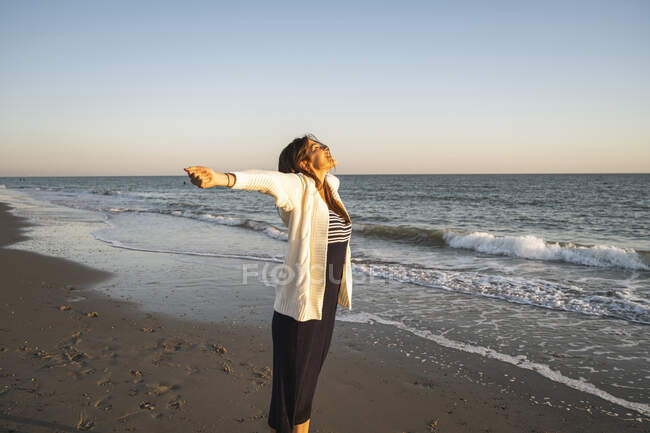 Carefree young woman standing at beach with arms outstretched during sunset - foto de stock