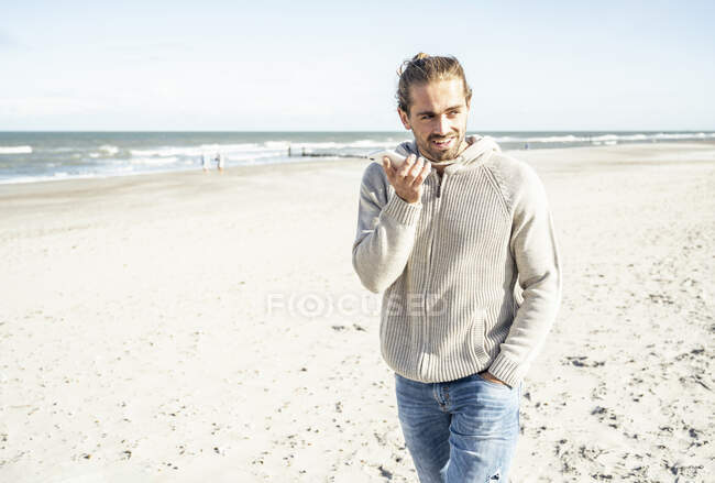 Man with hand in pocket talking on mobile phone while walking at beach during sunny day — Stock Photo