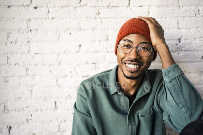 Hombre feliz con la cabeza en las manos contra la pared de ladrillo blanco - foto de stock