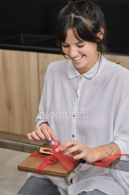 Retrato de mujer joven envolviendo regalo - foto de stock