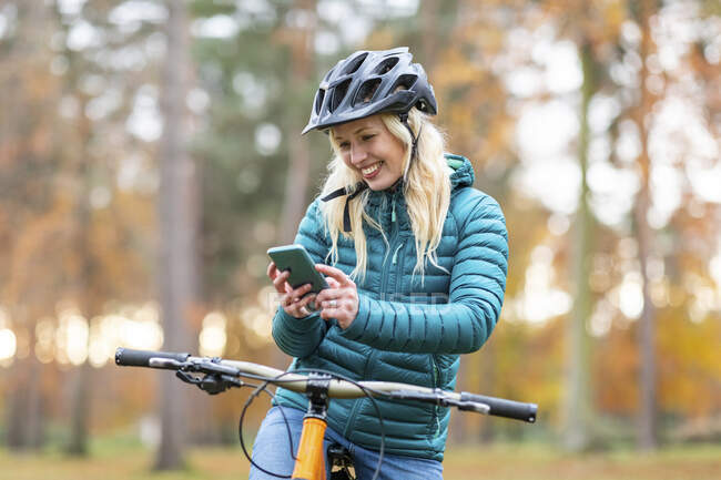 Happy woman with blond hair using mobile phone at Cannock Chase — Stock Photo