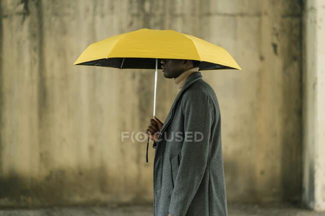 Молодий чоловік тримає жовту парасольку, стоячи навпроти стіни. — стокове фото