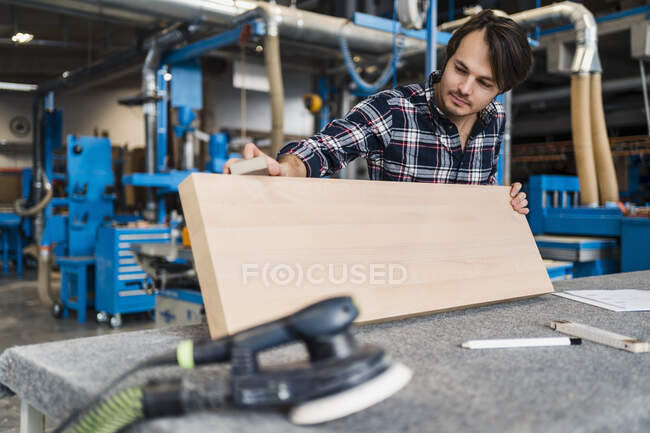 Trabalhador industrial medindo prancha de madeira enquanto em pé na indústria — Fotografia de Stock