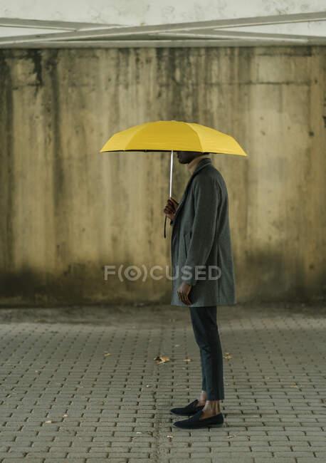 Homem vestindo casaco de pé com guarda-chuva no caminho — Fotografia de Stock