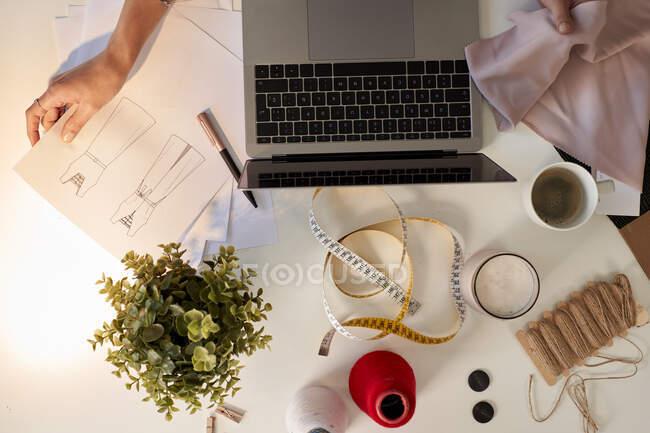 Diseñador de moda examinando la muestra de tela y el diseño de la computadora portátil en el escritorio en el taller - foto de stock