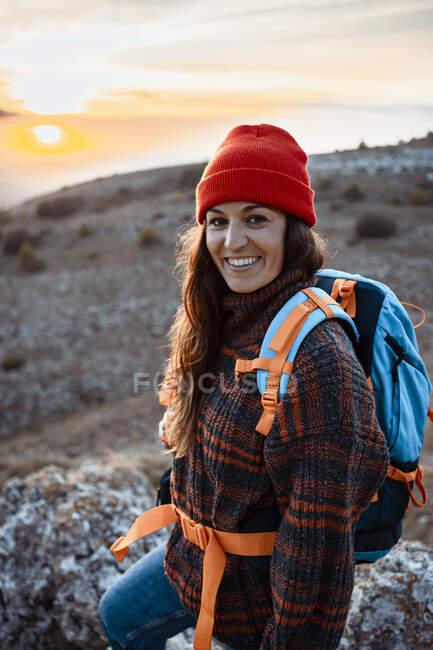 Felice escursionista donna con zaino in piedi sulla montagna durante il tramonto — Foto stock