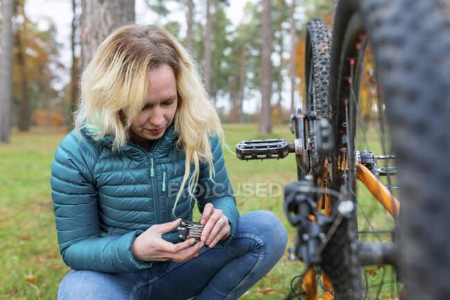 Mujer con cabello rubio reparando bicicleta en Cannock Chase - foto de stock