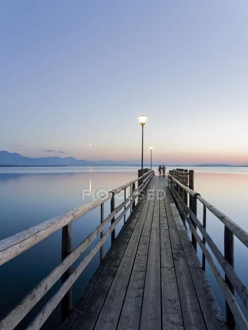Германия, Бавария, ясное небо над деревянным пирсом на берегу озера Кимзее в сумерках — стоковое фото