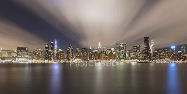 USA, New York, New York City, MidtownManhattan skyline illuminated at night seen across river — Stock Photo
