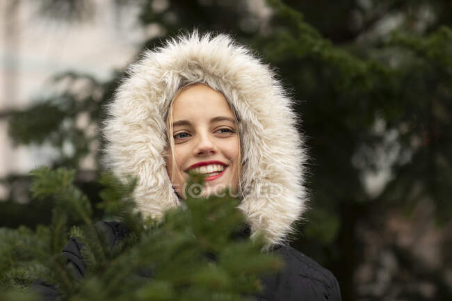 Smiling young woman in warm clothing day dreaming by tree during Christmas — Stock Photo