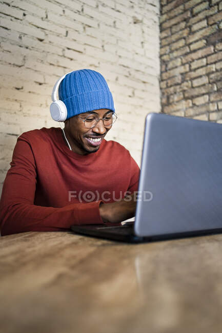 Smiling male professional using laptop while listening music through headphones on table — Stock Photo