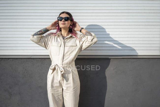 Забавна жінка з волоссям проти стіни в сонячний день. — стокове фото