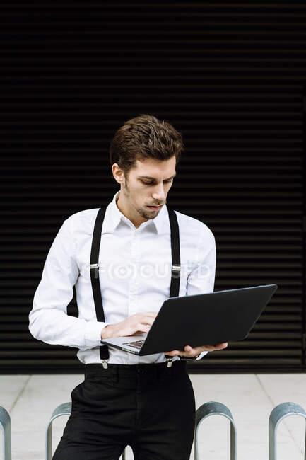 Elegante uomo d'affari che lavora sul computer portatile in città — Foto stock