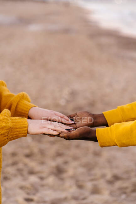 Close-up of man and woman hands clasped at beach — Stock Photo