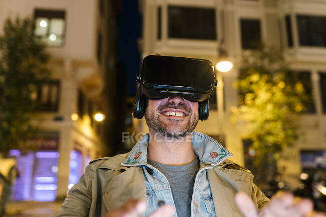 Happy man using virtual reality headset while sitting outdoors — Stock Photo