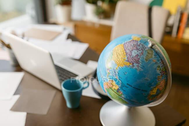 Глобус з ноутбуком і кухлем на столі. — стокове фото
