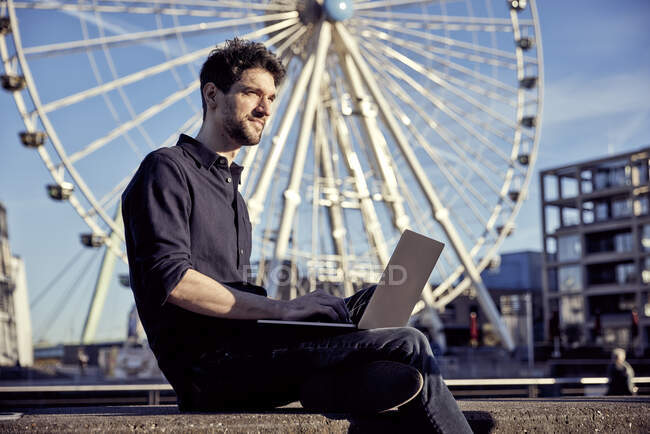 Businessman working on laptop while sitting against ferris wheel — Stock Photo