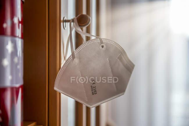 Close-up de máscara facial pendurado no botão em casa — Fotografia de Stock